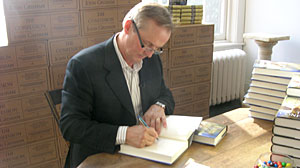 Photo: John Grisham autographs his latest novel