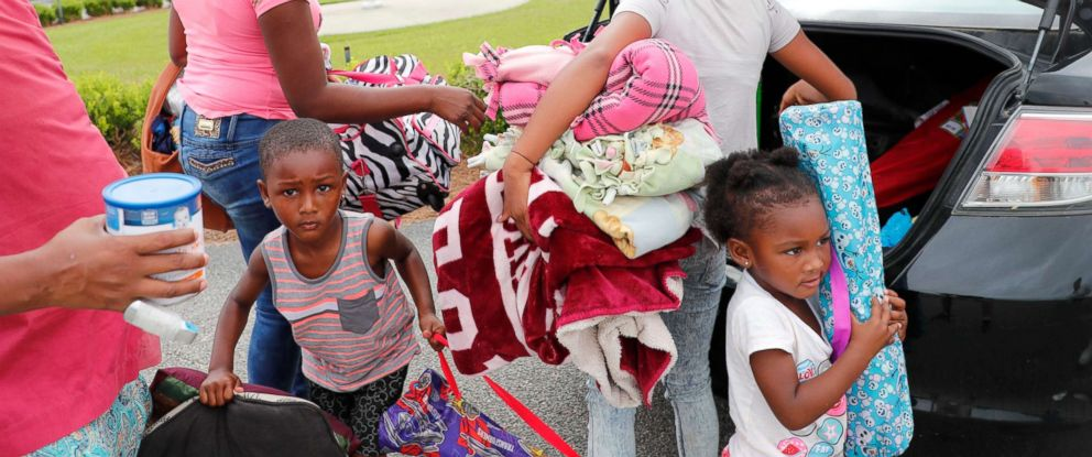 PHOTO: Shatika Young along with her children Jahmari, 3, left, and Samyah, 2, right, and niece Christina Young, 11, unpack after arriving at an evacuation shelter at Loris High School as Hurricane Florence approaches land in Loris, S.C., Sept. 13, 2018.