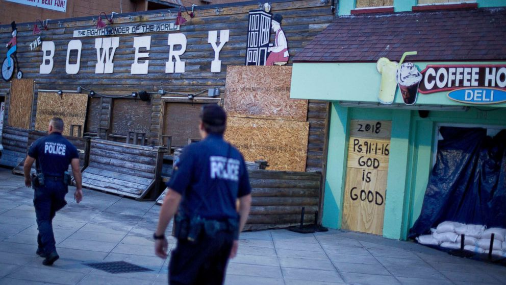 Police patrol past boarded up shops along the boardwalk in Myrtle Beach, S.C., Thursday, Sept. 13, 2018, as Hurricane Florence approaches the east coast.