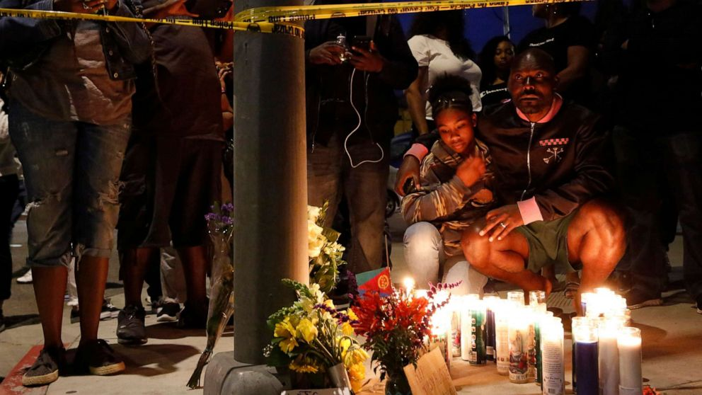 Haitian-French actor Jimmy Jean-Louis and his daughter Jasmin, 16, gather around candles set up across from the clothing store of rapper Nipsey Hussle in Los Angeles, March 31, 2019. Hussle, the skilled and respected West Coast rapper who had a decade-long success with mixtapes but hit new heights with his Grammy-nominated major-label debut album in 2018, was killed in a shooting.