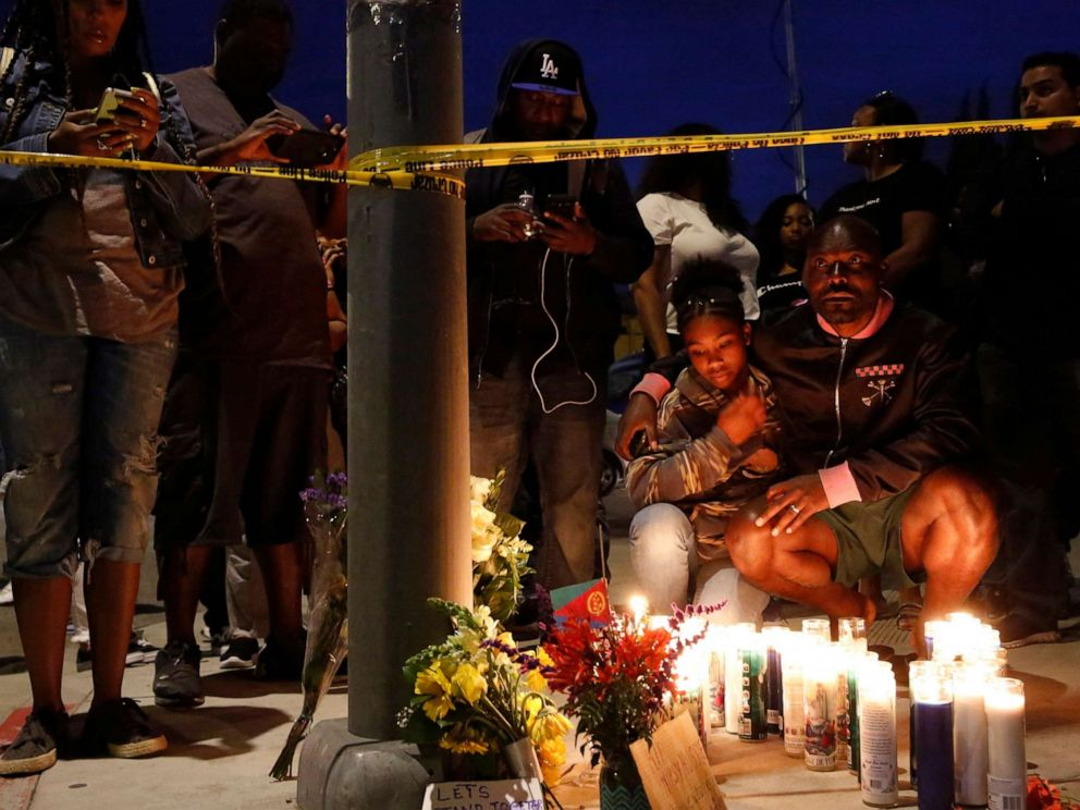 PHOTO: Haitian-French actor Jimmy Jean-Louis and his daughter Jasmin, 16, gather around candles set up across from the clothing store of rapper Nipsey Hussle in Los Angeles, March 31, 2019.