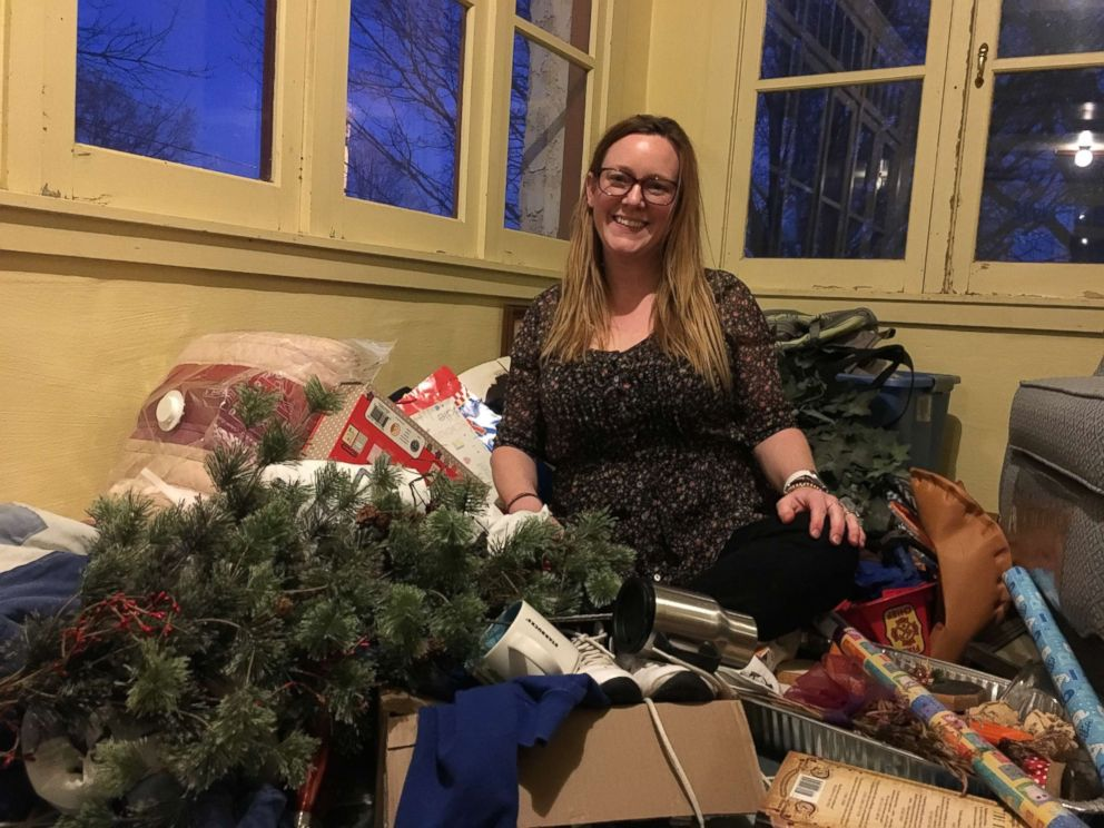 Jenni DeWitt sits among items she is sorting through in her Nebraska home.