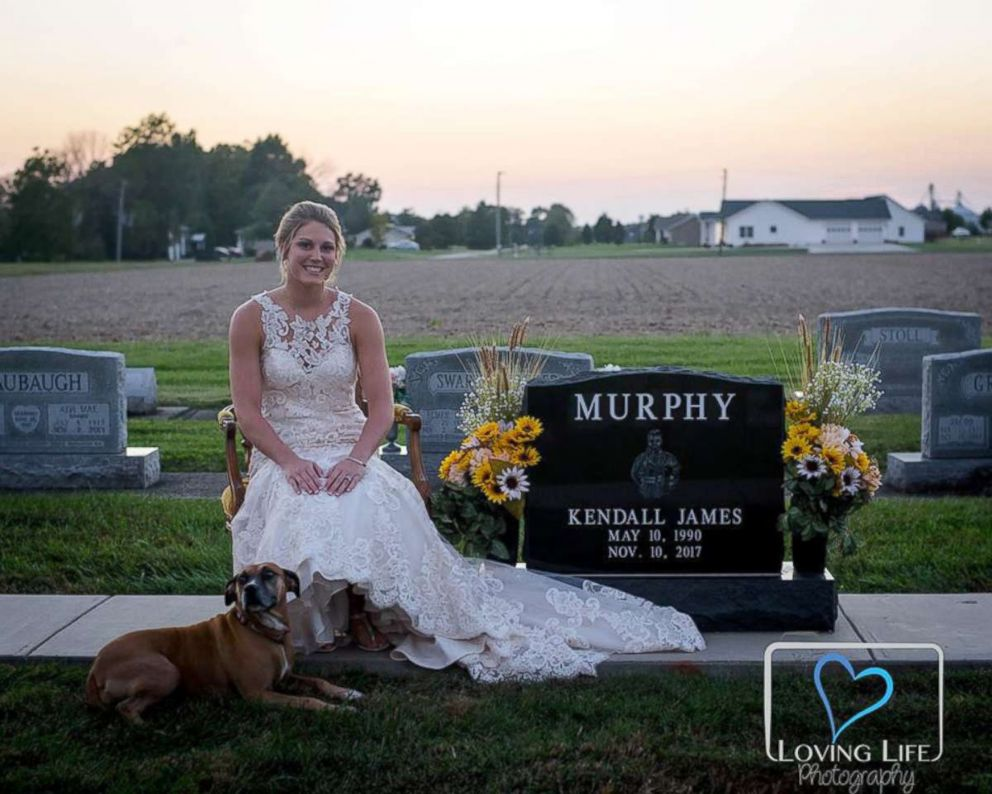 PHOTO: Jessica Padgett at Kendall Murphy's tombstone with his dog at Providence Mennonite Church grave site in Montgomery, Indiana, Sept. 29, 2018.