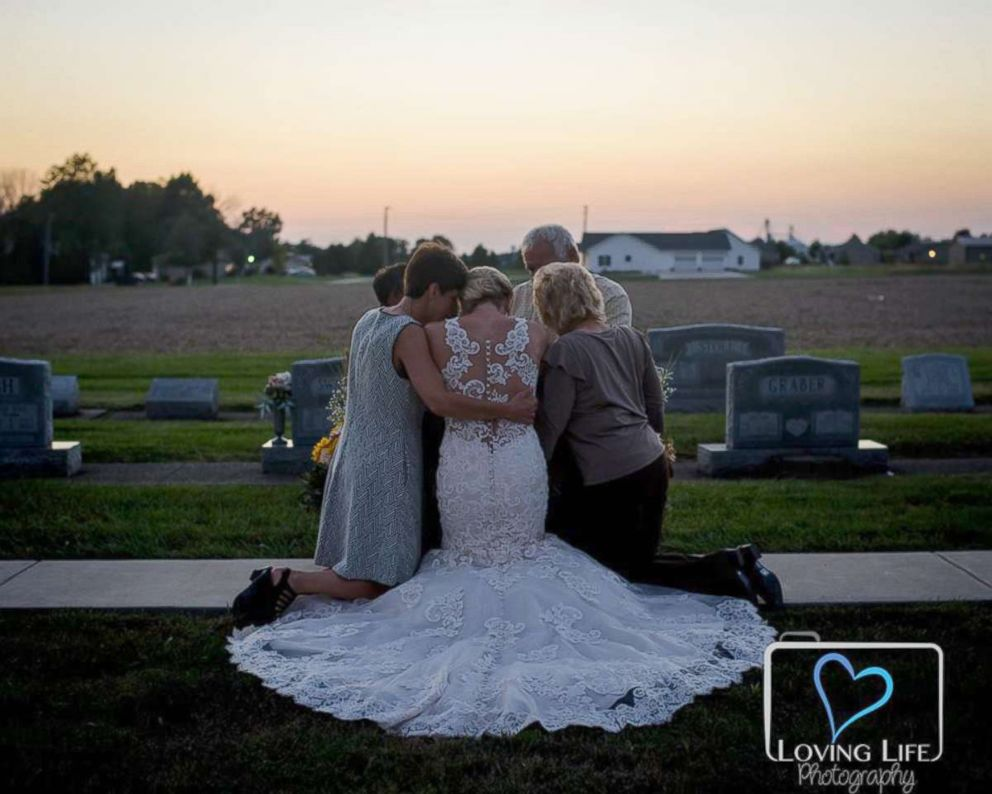PHOTO: Jessica Padgett with her family hugging at Kendall Murphys tombstone Providence Mennonite Church grave site, Sept. 29, 2018.