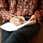 A woman writes in a journal in this undated stock photo.