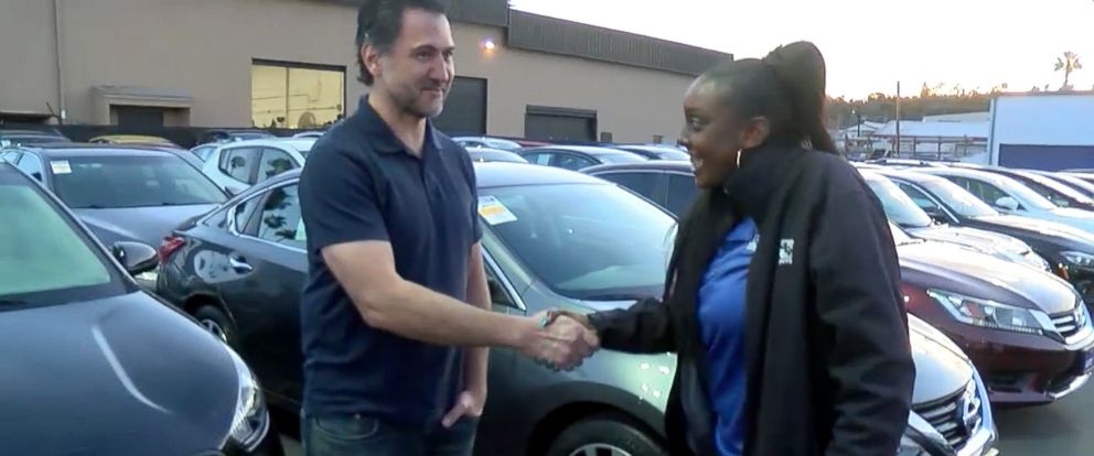 PHOTO: Kayla Cooper, 22, of San Diego, California, shakes hands with Dan Laguardia, 49, after he gave her his 2005 Scion instead of trading it in.