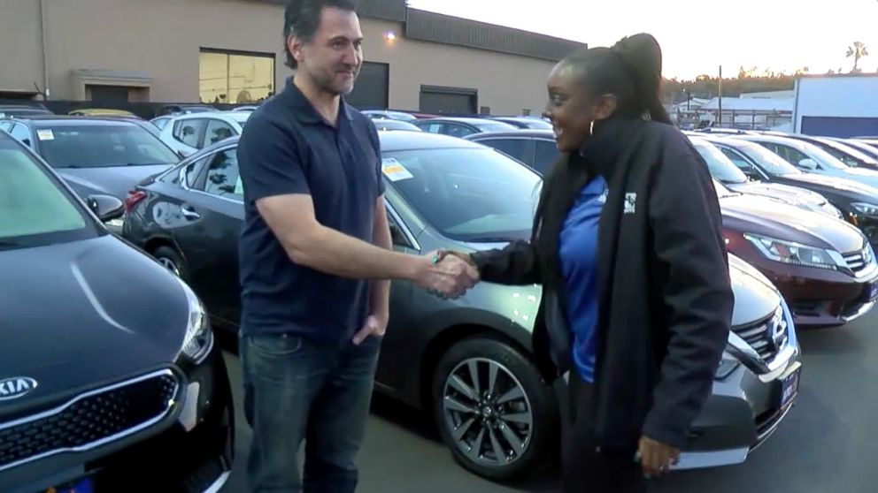 Kayla Cooper, 22, of San Diego, California, shakes hands with Dan Laguardia, 49, after he gave her his 2005 Scion instead of trading it in.