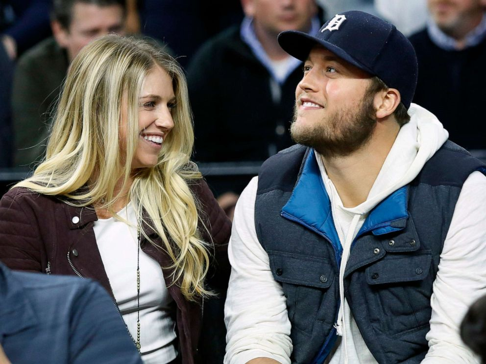 In this Nov. 17, 2015, file photo, Detroit Lions quarterback Matthew Stafford, right, smiles while watching the Detroit Pistons play the Cleveland Cavaliers with his wife Kelly, left, during the first half of an NBA basketball game, in Auburn Hills, Mich.