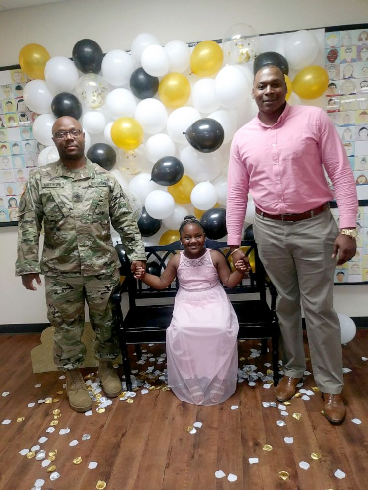 PHOTO: Kylar Matthews, 7, stands with her father, Kevin Matthews of the United States Army and her step-dad Kerlanders Watson, at Lamkin Elementary Schools daddy-daughter dance in Texas, March 29, 2019.