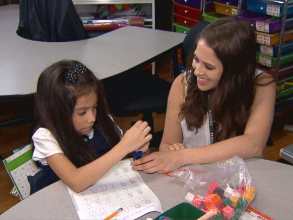 PHOTO: Kimber Bermudez works with a student at Carlos Fuentes Elementary in Chicago.