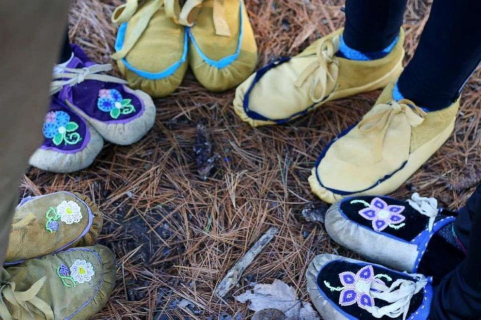 PHOTO: KwePack runners wearing moccasins stand in a circle in an undated handout photo.