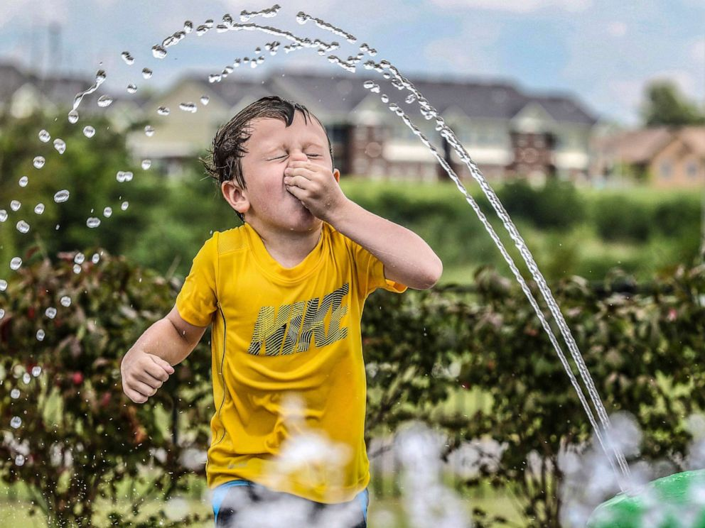 PHOTO: Owen Boarman, 3, holds his nose as he runs through water spray on a hot day, July 17, 2019, in Owensboro, Ky.