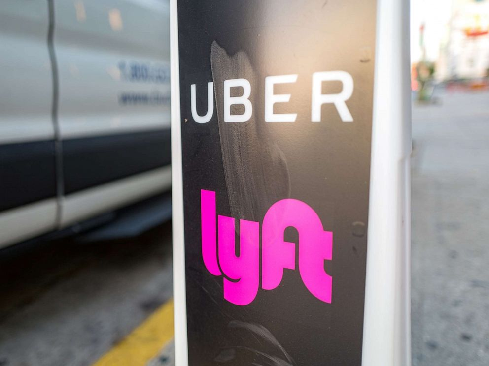 Close-up of vertical sign with logos for ridesharing companies Uber and Lyft indicating a location where rideshare pickups are available in downtown Los Angeles, Oct. 24, 2018.