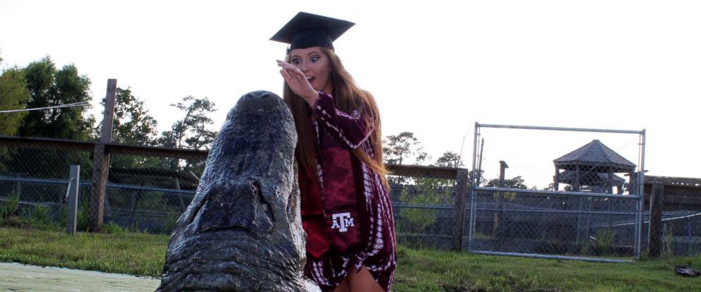 "PHOTO: Makenzie Holland took her Texas A&M graduation photos with ""Big Tex"" a gator she bonded with while interning at Gator Country Rescue."