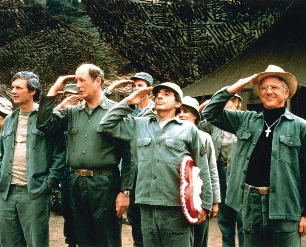 PHOTO: The cast of Mash salute in a publicity still, circa 1975.