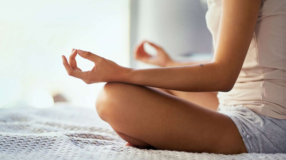 An undated stock photo depicts a young woman meditating at home.