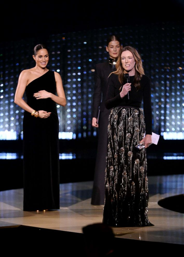 PHOTO: Clare Waight Keller is watched by Meghan, Duchess of Sussex and Rosamund Pike as she speaks after receiving the award for British Designer of the Year Womenswear Award for Givenchy during The Fashion Awards 2018 in London, Dec. 10, 2018.