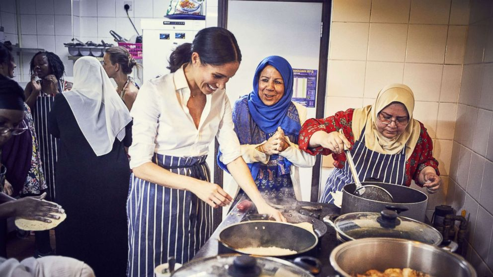 This undated handout image released by Kensington Palace on Sept. 17, 2018 shows, Meghan Markle, Duchess of Sussex cooking with women in the Hubb Community Kitchen at the Al Manaar Muslim Cultural Heritage Centre in West London, in the aftermath of the Grenfell Tower fire, which has resulted in the publications of Together: Our Community Cookbook.