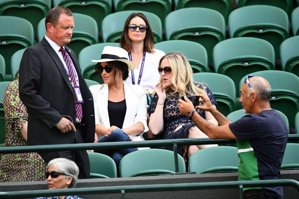 PHOTO: A spectator is reprimanded by a security guard after taking a photograph near Meghan, Duchess of Sussex, on Court 1 of Wimbledon Tennis Championships, Day 4, at The All England Lawn Tennis and Croquet Club in London, July 4, 2019.