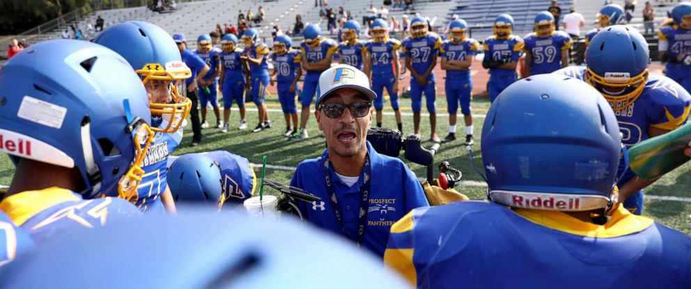 PHOTO: Rob Mendez, the head coach for the Prospect High School Junior Varsity football team, talks to his team in the huddle during their first game of the season against Santa Clara High School, Aug. 24, 2018, in Saratoga, Calif.