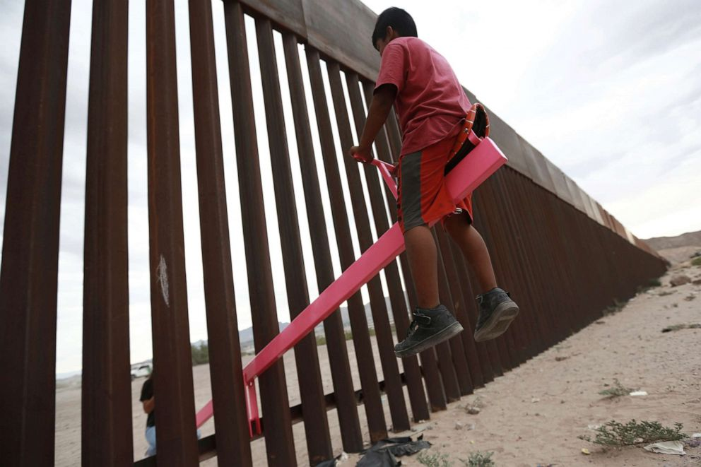 PHOTO: A child plays on a seesaw installed between the border fence that divides Mexico from the United States in Ciudad de Juarez, Mexico, July 28, 2019. The seesaw was designed by Ronald Rael, a professor of architecture in California.