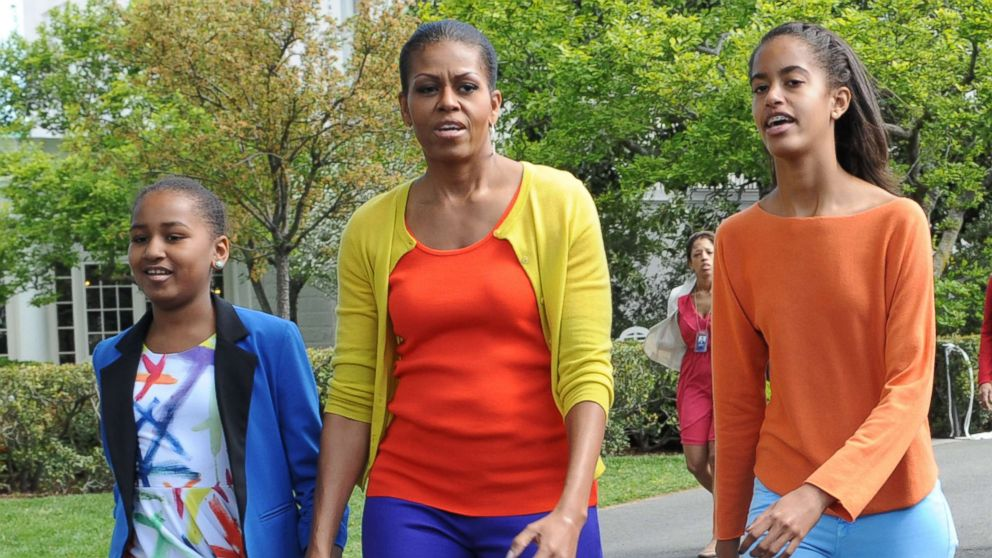 First lady Michelle Obama walks with daughters Sasha and Malia at the annual White House Easter Egg Roll in Washington, April 9, 2012.