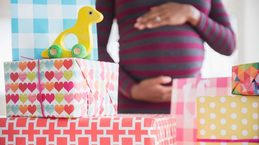 A pregnant woman is surrounded by gifts in an undated stock photo.