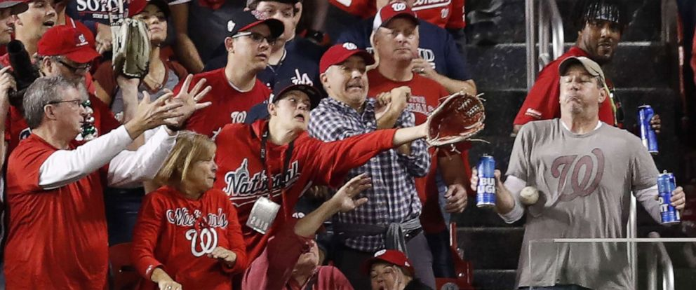 PHOTO: Houston Astros batter Yordan Alvarezs two run home run hits a fan holding two beers (R) in the stands in the top of the second inning of their MLB 2019 World Series game five at Nationals Park in Washington, Oct. 27 2019.