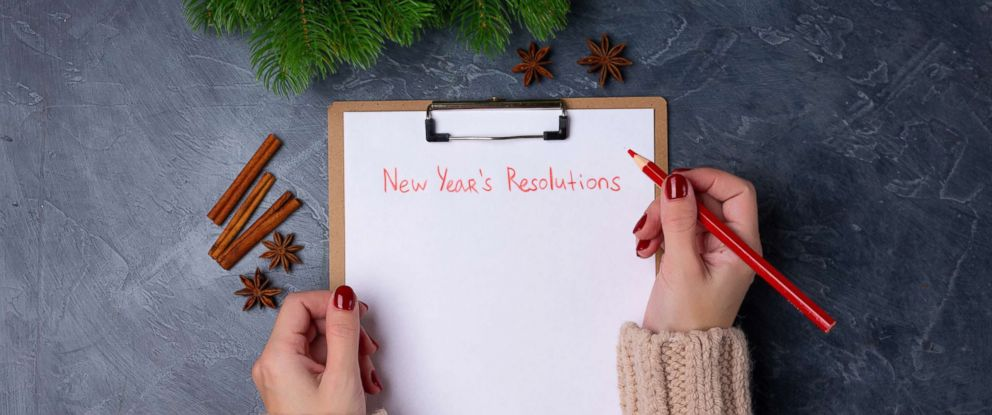 PHOTO: A woman holds a pencil in front of an empty list of New Years resolutions in an undated stock photo.