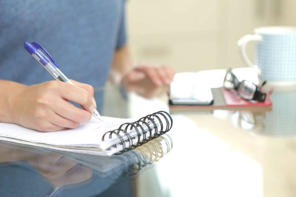 A woman writes in a notebook in this undated stock photo.
