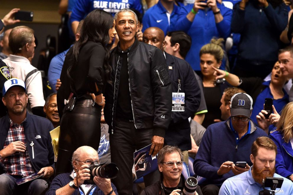 Former President Barack Obama talks with ESPN analyst Maria Taylor while attending the game between the North Carolina Tar Heels and the Duke Blue Devils at Cameron Indoor Stadium, Feb. 20, 2019, in Durham, N.C.