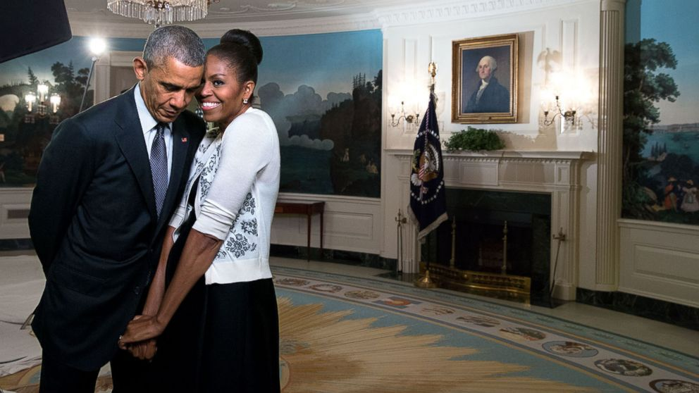 First lady Michelle Obama snuggles with President Barack Obama during a video taping in the Diplomatic Reception Room of the White House, March 27, 2015.