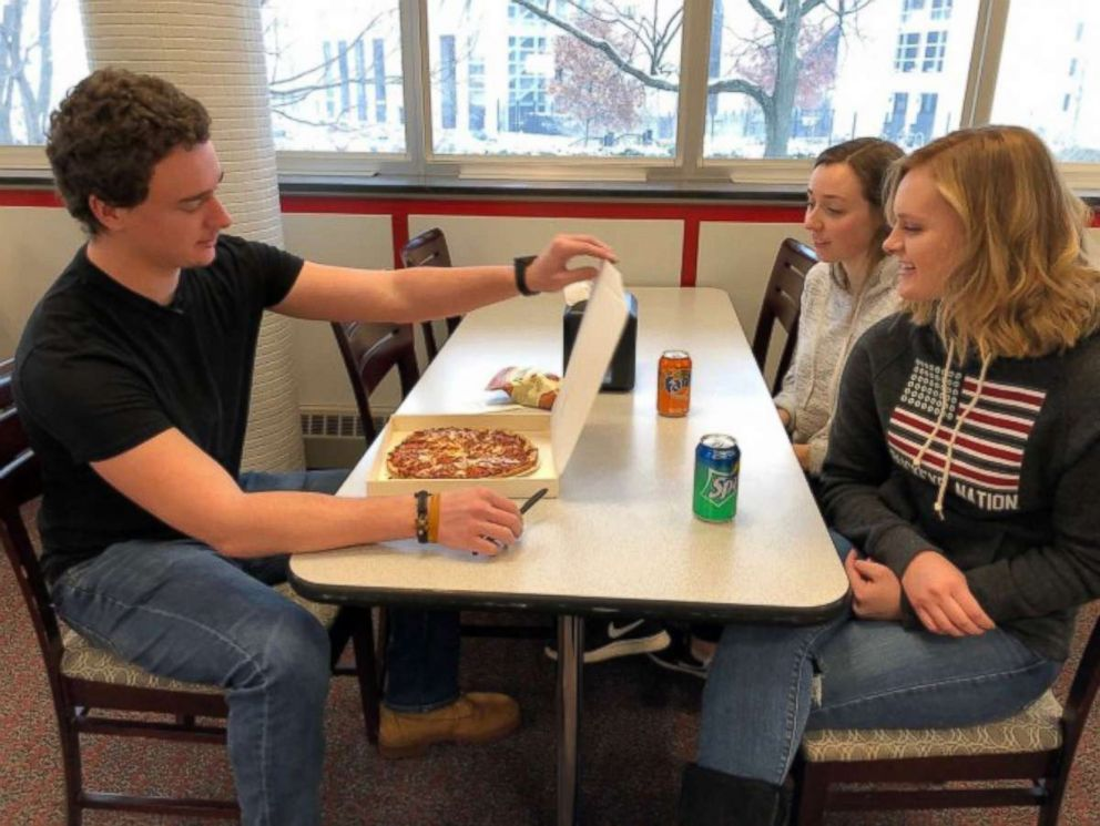 PHOTO: Students enjoy a warm pizza from the pizza ATM.