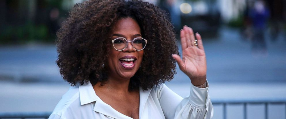PHOTO: Oprah Winfrey waves as she arrives to the opening celebration of the Statue of Liberty Museum on Liberty Island in New York, May 15, 2019.