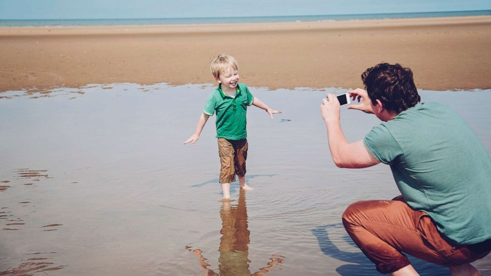 Child at  beach with dad taking picture