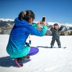 A woman takes a photo of a child in an undated stock photo.