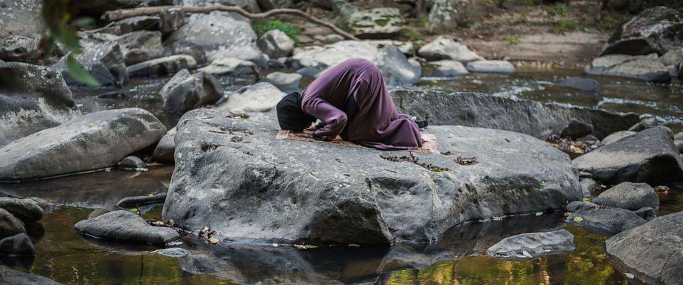 PHOTO: A woman prays on a flat rock in Rock Creek Park in Washington, D.C.