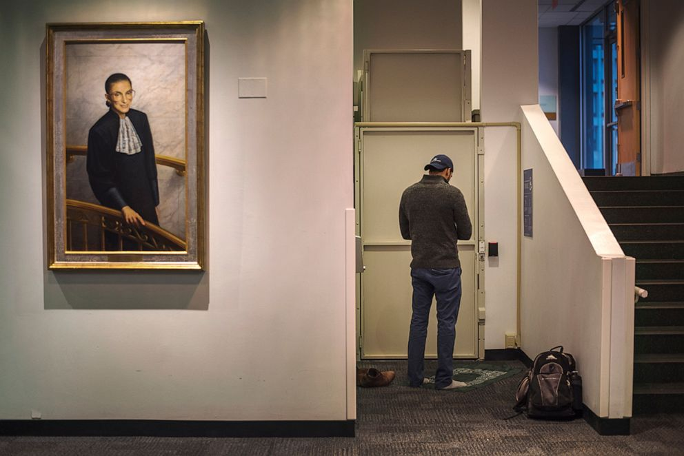 PHOTO: A man prays next to a portrait of Supreme Court justice Ruth Bader Ginsburg at the Columbia University Law School.