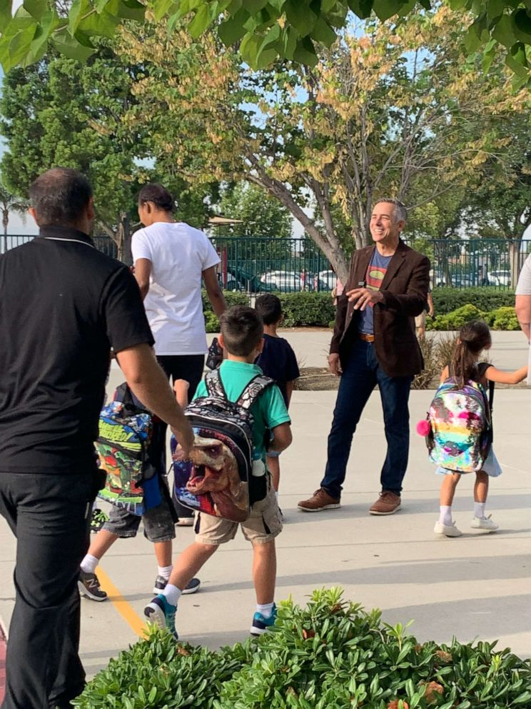 PHOTO: Jeff Sipos kicked off the new school year Aug. 5 by exchanging hugs and high fives with pupils and their families outside John L. Golden Elementary School in Rancho Cucamonga, California.