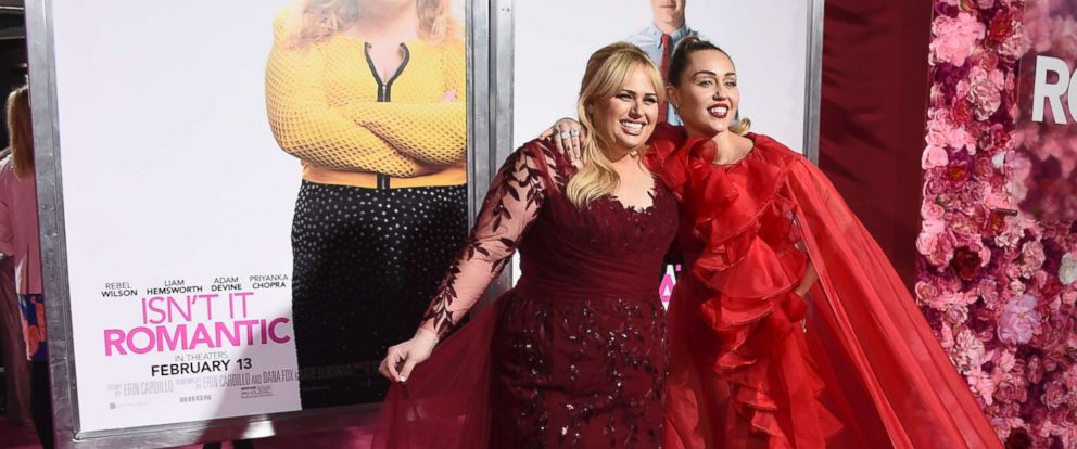 """PHOTO: Cast member Rebel Wilson and Miley Cyrus arrive at the Los Angeles premiere of """"Isnt It Romantic"""" at The Theatre at Ace Hotel, Feb. 11, 2019."""