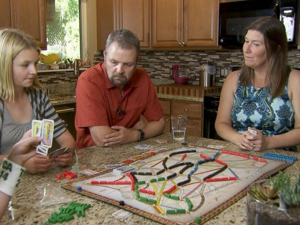 PHOTO: Carl and Mindy Jensen play a board game with their two children.