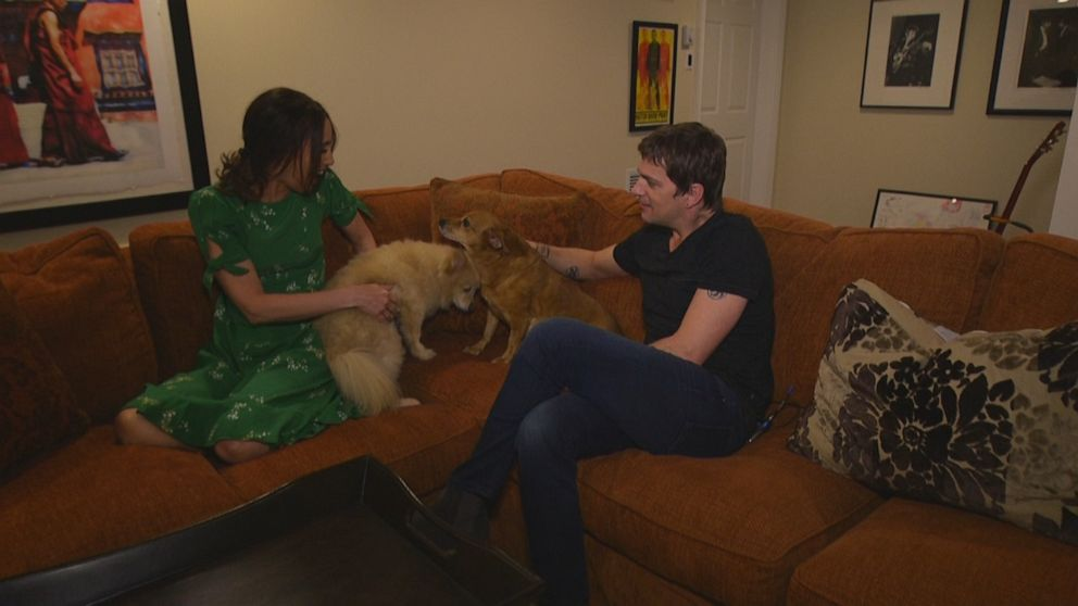 PHOTO: Marisol and Rob Thomas play with their two dogs in their home.