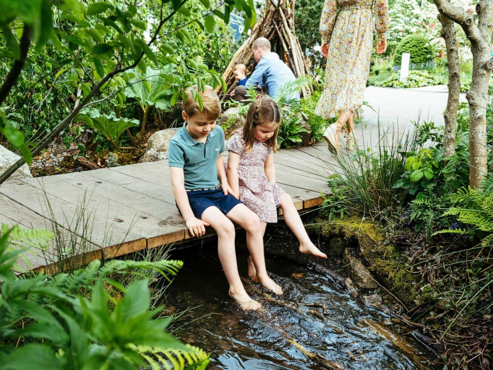 PHOTO: Prince William, Kate, Duchess of Cambridge and their children, Prince George, front, Princess Charlotte, front, and Prince Louis play in the Adam White and Andree Davies co-designed garden, in this image released on May 19, 2019.