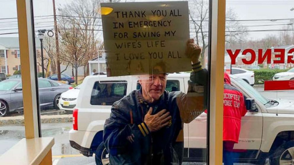 Man holds sign at emergency room's window thanking hospital workers for saving his wife's life