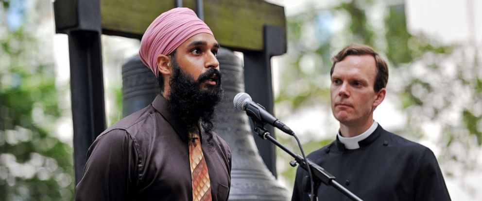 PHOTO: Simran Jeet Singh (left) of the Sikh Coalition speaks as the Reverend Matthew Heyd of Trinity Wall Street listens in the courtyard of St. Pauls Chapel in New York on Aug. 10, 2012.