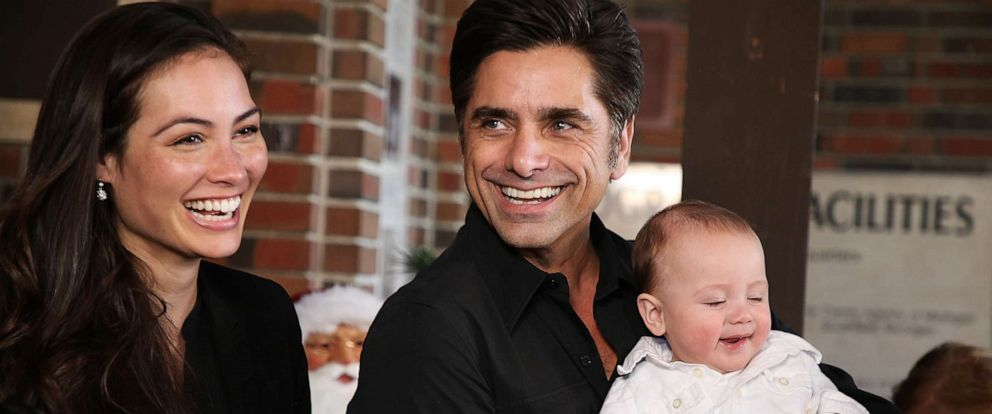 PHOTO: John Stamos holds his son, Billy, as his wife Caitlin McHugh smiles at an event in Beaumont, Calif., Nov. 27, 2018.