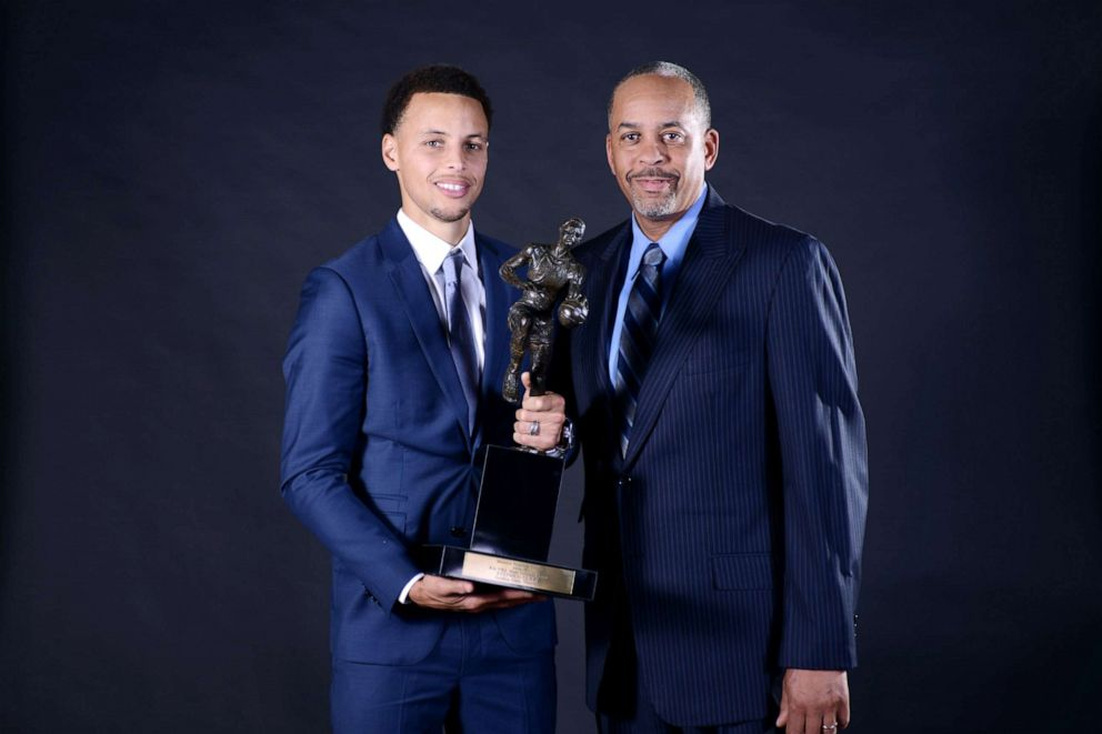 PHOTO: Stephen Curry #30 of the Golden State Warriors poses for a portrait with the Maurice Podoloff Trophy alongside father Dell Curry at the 2014-15 KIA Most Valuable Player Award Press Conference, May 4, 2015, at Oakland, Calif.