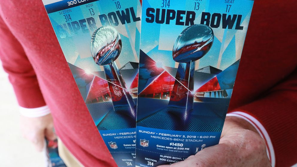 A football fan shows off his Super Bowl tickets after picking them up at the Mercedes-Benz Stadium ticket window on Jan. 22, 2019, in Atlanta.