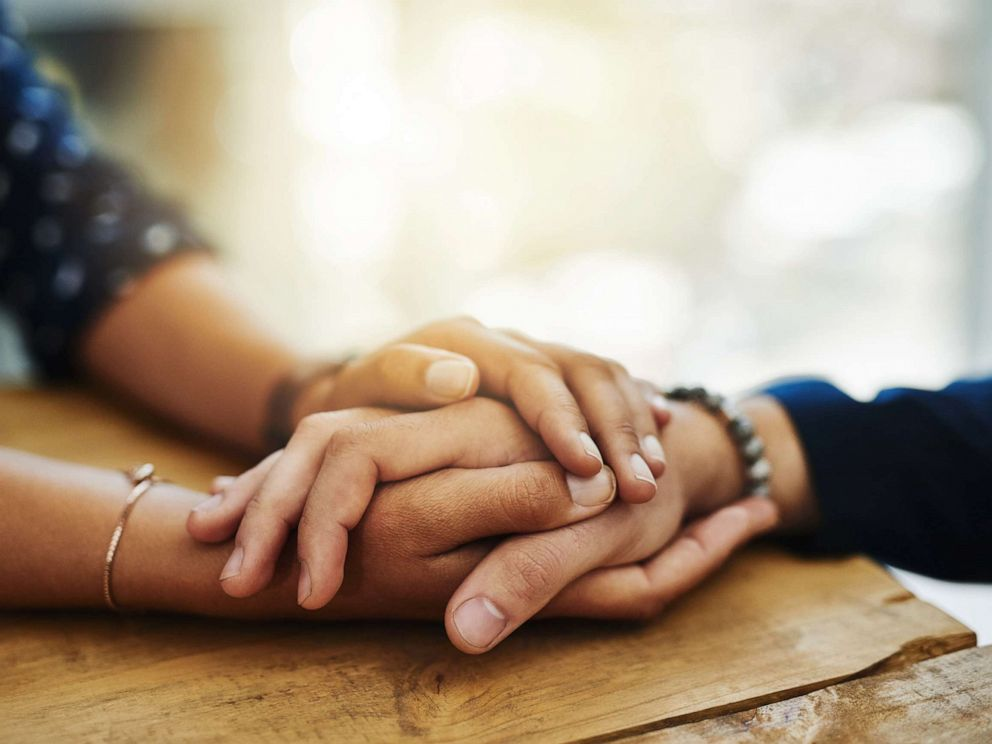 PHOTO: An undated stock photo depicts two people holding hands in comfort.