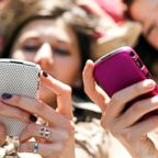 This stock image depicts two teen girls on their cellphone.
